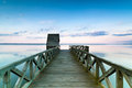Wooden pier on calm lake at sunset colorful over viewed from a bridge Royalty Free Stock Photography