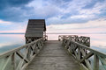 Wooden pier on calm lake at sunset colorful over viewed from a bridge Stock Images
