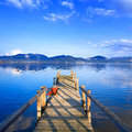 Wooden pier or jetty on a blue lake sunset and sky reflection on Royalty Free Stock Image