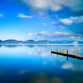 Wooden pier or jetty and on a blue lake sunset and sky reflection on water versilia tuscany italy cloudy long exposure Stock Photography