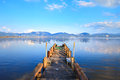 Wooden pier or jetty and on a blue lake sunset and sky reflection on water versilia tuscany italy massaciuccoli Royalty Free Stock Image
