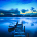 Wooden pier or jetty and a boat on a lake sunset versilia tusca sky reflection water long exposure massaciuccoli tuscany italy Royalty Free Stock Photo