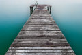 Wooden pier or jetty on lake garda in italy photo taken with long exposure time to create a silky water effect Royalty Free Stock Image