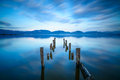 Wooden pier or jetty remains on a blue lake sunset and sky reflection on water versilia tuscany italy cloudy long exposure Royalty Free Stock Photography