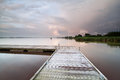 Wooden pier on lake during shower at sunset Royalty Free Stock Photo