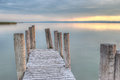 Wooden pier on the lake at sunset with columns Stock Photo