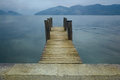 Wooden pier on lake. Vacation, tourism and adventure concept. Retro filter Royalty Free Stock Photo