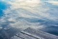 Wooden pier in the reflections of the sky Royalty Free Stock Photo