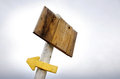 Wooden placard a arrow blank and pointing left pinned to post against s dull sky Stock Photos