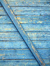Wooden planks with old blue paint as background fragment of wall horizontal boards nailed diagonal slats painted texture closeup Royalty Free Stock Photo