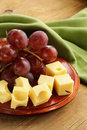 Wooden plate with cheese maasdam and grapes red Stock Photo
