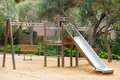 Wooden playground with metal slide Stock Photo