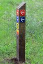 Wooden pole, sign, with colorful direction signs, arrows Royalty Free Stock Photo