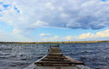 Wooden pontoon bridge across the water the river ponds summer weather blue sky and clouds Royalty Free Stock Photos
