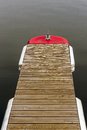 Wooden pontoon with red cap on blue water Royalty Free Stock Photography