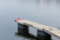 Wooden pontoon with red cap and bollards on blue water Royalty Free Stock Images