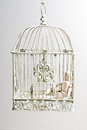 Wooden puppet in bird cage sitting Royalty Free Stock Photo