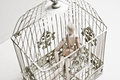 Wooden puppet in bird cage sitting sad Royalty Free Stock Photo