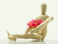 The wooden puppet sitting and hugging pink flowers.On a white backdrop Royalty Free Stock Photo