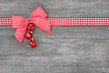 Wooden red christmas background with a white checked ribbon decoration on Royalty Free Stock Images