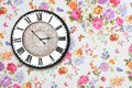 Wooden retro clock on floral wallpaper Royalty Free Stock Photography