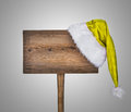 Wooden road sign with santa hat on grey background Stock Photos