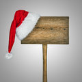 Wooden road sign with santa hat isolated on a gray background Stock Photos