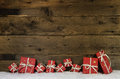 Wooden rustic background with red christmas presents. Royalty Free Stock Photo