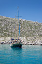 Wooden sailboat anchored in a cove of greek island Stock Photo