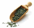 Wooden scoop with green tea dried Stock Image