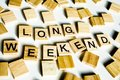 Wooden scrabble letters spelling the word LONG WEEKEND on white backround. Royalty Free Stock Photo