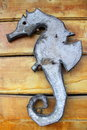 Wooden seahorse cropped from a piece of wood and nailed to a wall Stock Photo
