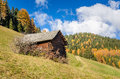 Wooden shed in the alps and blue sky along a track autumn Stock Photo