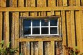 Wooden shed window small in yellow wall Stock Images