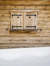 Wooden shutters on a cabin window with snowdrift in foreground detail of rustic heart shapes and falling snowflakes and Stock Photo
