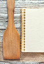 Wooden spatula notebook and ribbon on the old background Stock Image