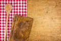 Wooden spoon and book on a wooden board with checkered tablecloth Royalty Free Stock Images