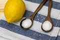 Wooden spoon with citric acid on striped tablecloth close up Stock Images