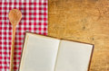 Wooden spoon and cookbook on a wooden board with checkered tablecloth Stock Photography