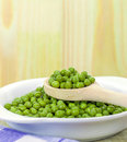 A wooden spoonful of fresh green peas with copy space background Stock Images
