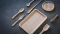 Wooden spoons and plate on dark gray gypsum on desktop Royalty Free Stock Photo
