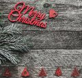 Wooden square background. Red Merry Christmas inscription, text space, and a fir tree crest. Top view Royalty Free Stock Photo