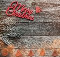 Wooden square background. Red Merry Christmas inscription, text space and a fir tree. Top view Royalty Free Stock Photo