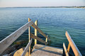 Wooden staircase to the water leading clear blue for a summer bath outdoors Royalty Free Stock Photo