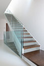 Wooden stairs with glass balustrade in modern interior and white epoxy flooring Stock Photography