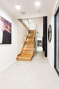 Wooden stairs through the hallway in a luxury house illuminated at night Royalty Free Stock Photo