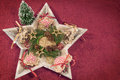 Wooden star on red background decorated with Christmas wreath