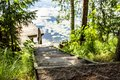 Wooden steps lead to the river and the pier, among grass and trees, on a sunny summer day, in the countryside Royalty Free Stock Photo
