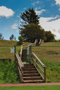 Wooden steps lead up a grassy hill with a cyclone fence nearby Stock Image