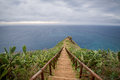 Wooden steps path from Cristo Rei statue to the ocean cape. Royalty Free Stock Photo